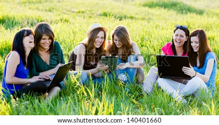 Girlfriends having fun outdoors using wireless internet on their laptops and tablet.