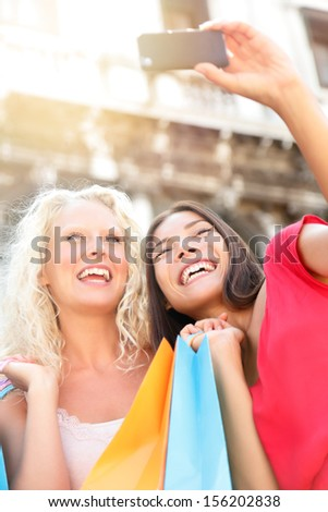 Girlfriends shopping laughing happy taking photo with smartphone. Woman friends holding shopping bags while taking self-portrait picture outdoor. Blonde girl and multiracial Asian Caucasian woman, 20s - stock photo