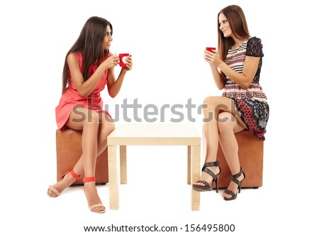 Girlfriends sitting at the table and holding cups of tea, talking and gossiping isolated on white - stock photo