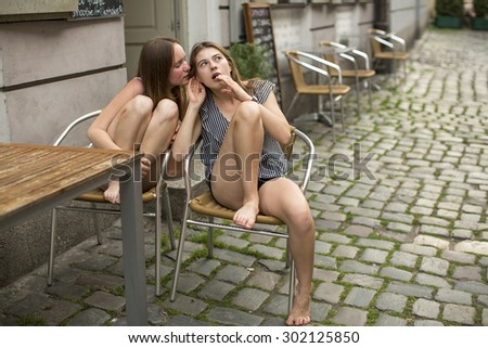 Girlfriends teenage girls gossiping while sitting in a street cafe. - stock photo
