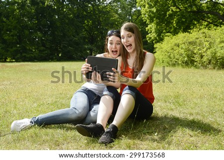 Girlfriends with tablet in park, amazed