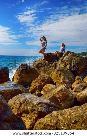 Girls after a shipwreck on the rocks - stock photo