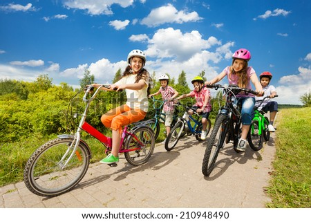 Girls and boys in helmets ride bikes together