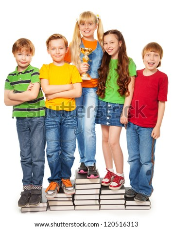 Girls and boys standing on books holding their award