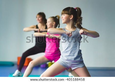 Girls and Instructor or mother doing gymnastic exercises  in fitness class - stock photo