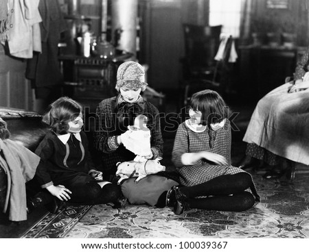 Girls and mother on floor with doll