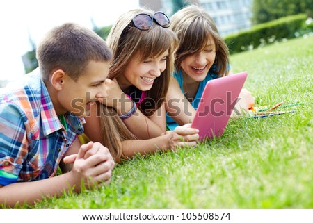 Girls and their male friend enjoying summer warmth and laughing at the sight of funny pictures on the pad screen - stock photo