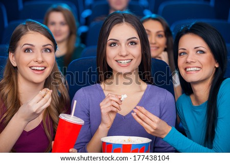 Girls at the cinema. Happy young women eating popcorn and drinking soda while watching movie at the cinema together - stock photo