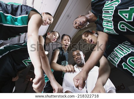 Girls basketball team in huddle with coach - stock photo