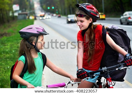 Girls children cycling on yellow bike lane. There are cars on road.