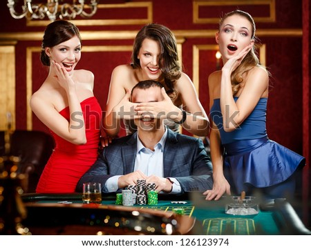Girls cover the eyes of the gambler playing roulette at the casino - stock photo