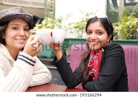 Girls doing cheers with their coffee mugs in a restaurant. - stock photo