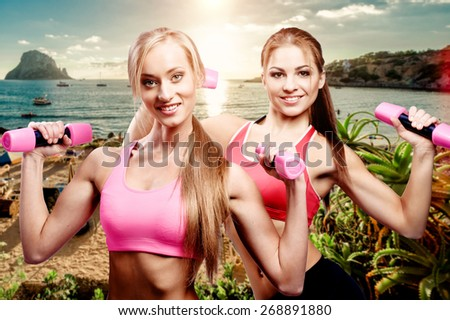 Girls doing fitness exercise with dumbbells against beach background - stock photo