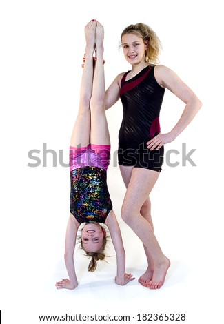 Girls doing gymnastic moves while one is standing on her head and other helping - stock photo