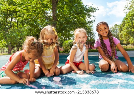 Girls draw image with chalk on playground - stock photo