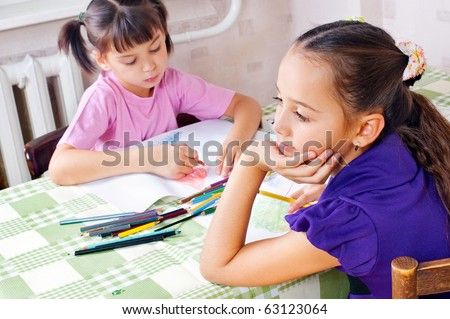 Girls drawing with crayons at the table