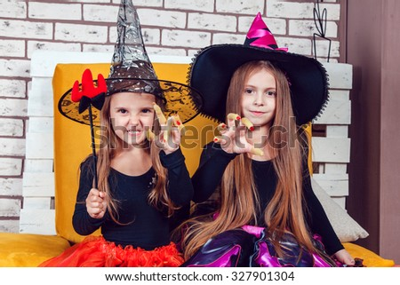 Girls, dressed up in Halloween costumes, show emotions of witches and vampires.