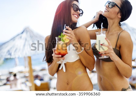 Girls drinking cocktails on beach in bikinis - stock photo
