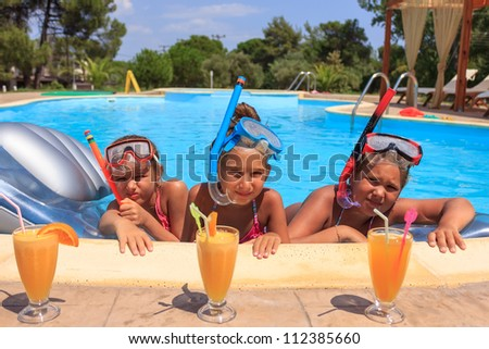 Girls drinking juice in the swimming pool - stock photo