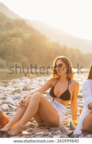 Girls enjoy in summer sun by the river - stock photo