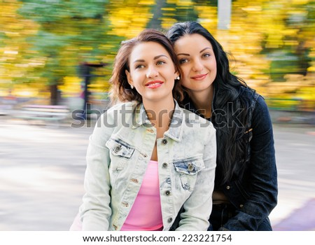 girls friends laughing and outdoor on the carousel - stock photo