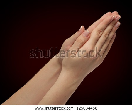 girls hands folded in prayer isolated on black - stock photo