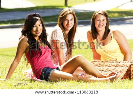 Girls having a pic nic in a park - stock photo