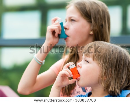 Girls having asthma using asthma inhaler for being healthy - Asthma attack - allergy concept -  shallow depth of field - stock photo