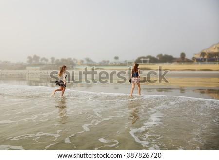 Girls having fun in ocean waves on a foggy morning, Daytona Beach Florida, USA. - stock photo