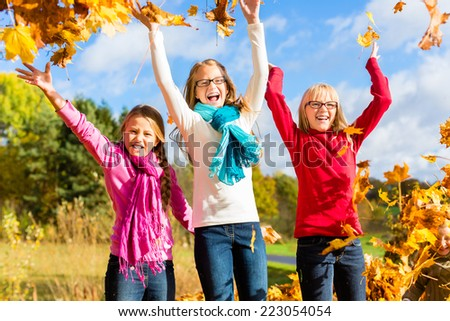 Girls having fun throwing fall or autumn leaves in park  - stock photo