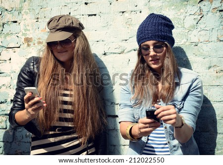 Girls having fun together outdoors and calling smart phone, lifestyle. Instagram effect. - stock photo