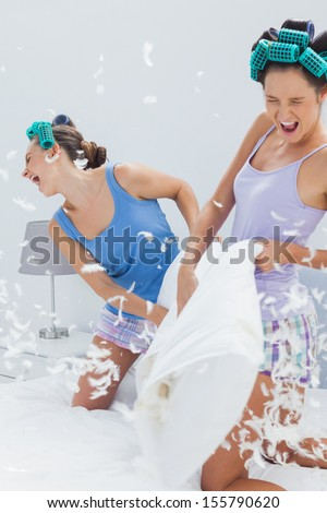 Girls having pillow fight at slumber party - stock photo