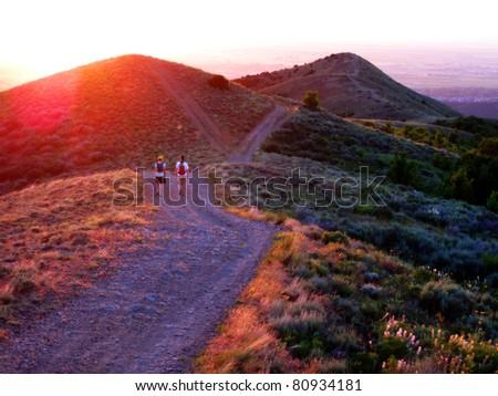 Girls hiking along a mountain at sunrise or sunset - stock photo