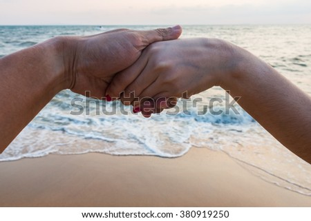 Girls holding hands backdrop of the sea