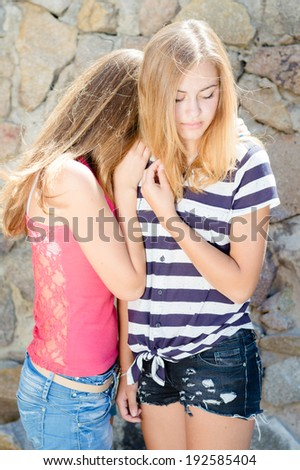 Girls Hug: image of 2 young women teenage girl friends embracing for comfort on summer day at stone wall - stock photo