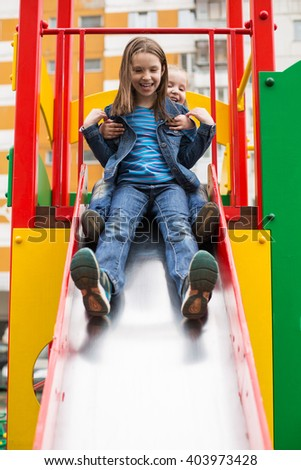 Girls in jeans suits slides down the hill on the playground