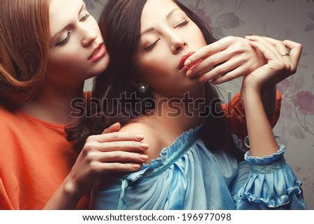 Girls in love concept. Portrait of two gorgeous girlfriends in blue and orange retro dresses making love in hotel room. Perfect skin, great make-up. Vintage style. Close up. Studio shot - stock photo