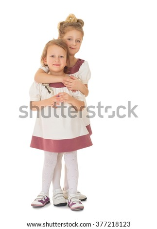 Girls in matching dresses hug - Isolated on white background
