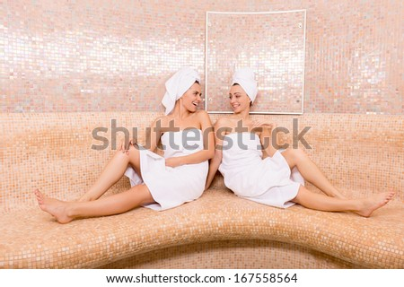Girls in sauna. Two attractive young women wrapped in towel talking to each other and smiling while spending time in sauna - stock photo