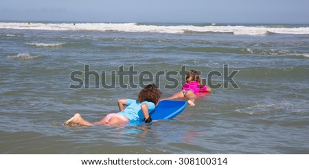 Girls in the ocean surfing at summer