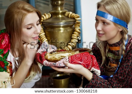 Girls in the Russian national costumes with pancakes - stock photo
