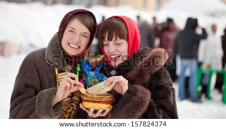 Girls in traditional  clothes tasting pancake  during  Shrovetide - stock photo