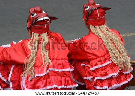 Girls in traditional Peruvian dress wear devil masks at a festival in the Plaza Mayor, in Lima, Peru