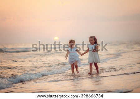 Girls in white dresses are on the beach at sunset - stock photo