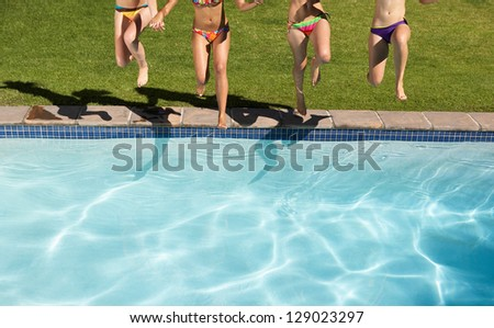 girls jump at the water pool