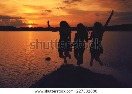 girls jump in the lake at sunset in summer