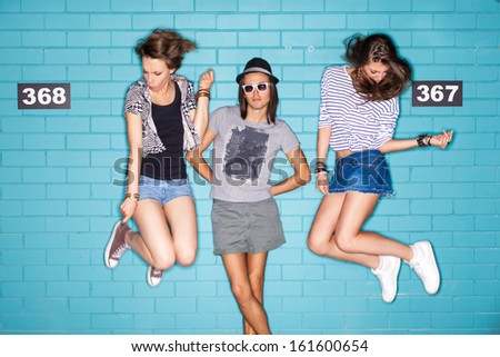 girls jump playing air invisible guitar while boy in hat and sunglasses poses for the camera in front of blue brick wall - stock photo