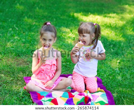 Girls kids sisters friends teasing sitting on grass, eating ice cream  - stock photo