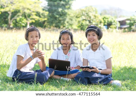 girls learning internet with notebook and tablet from sharing mobile telephone on the grass