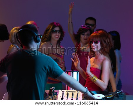 girls looking at dj and dancing, with sunglasses on, with other people partying in the background